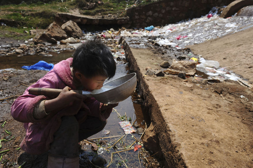 15. Child Drinks Water From Stream